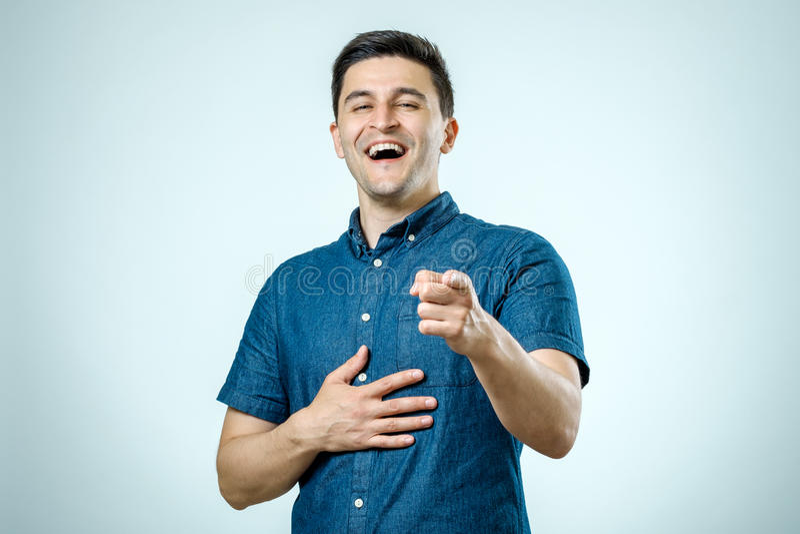 Homem novo feliz do retrato, rindo, apontando com o dedo em algum fotos de stock royalty free