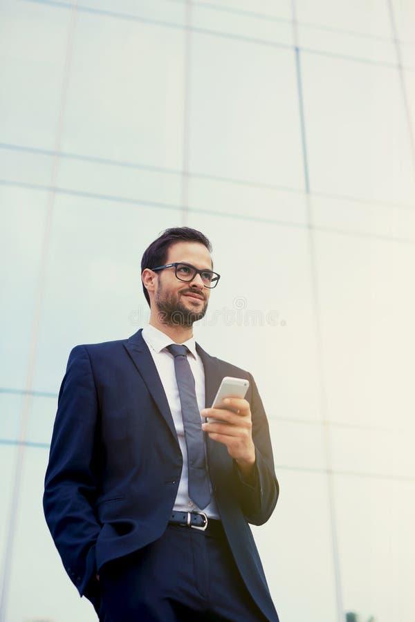 Homem novo feliz em um terno à moda e nos óculos de sol que estão na frente dos escritórios com telefone foto de stock royalty free