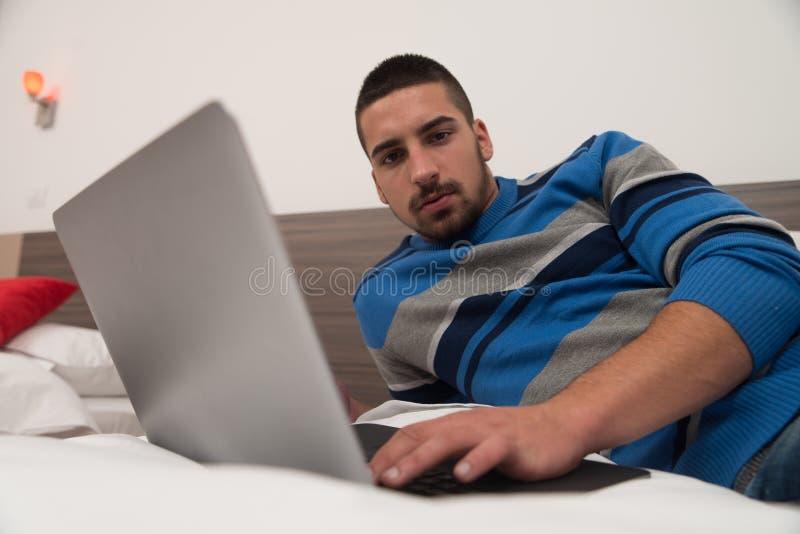 Homem novo feliz na cama usando o portátil imagens de stock royalty free