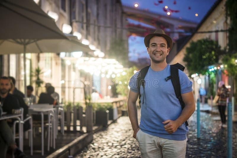 Homem novo feliz na camisa azul que anda sobre na cidade no evev fotografia de stock