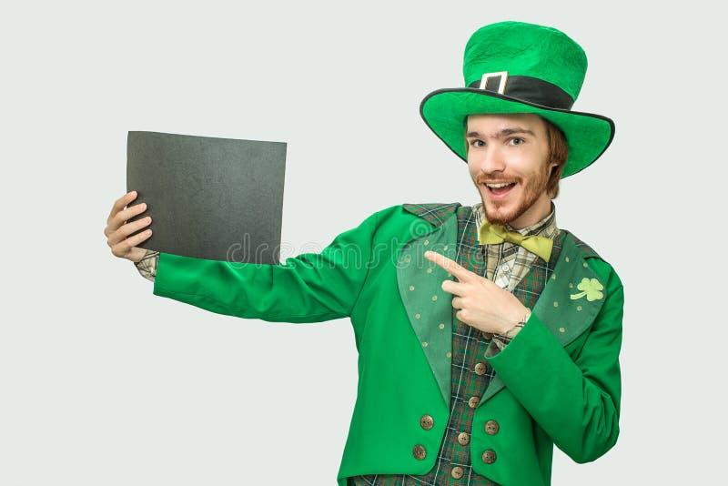 Homem novo feliz no terno verde que guarda o pedaço de papel preto Veste o terno de St Patrick no fundo cinzento foto de stock