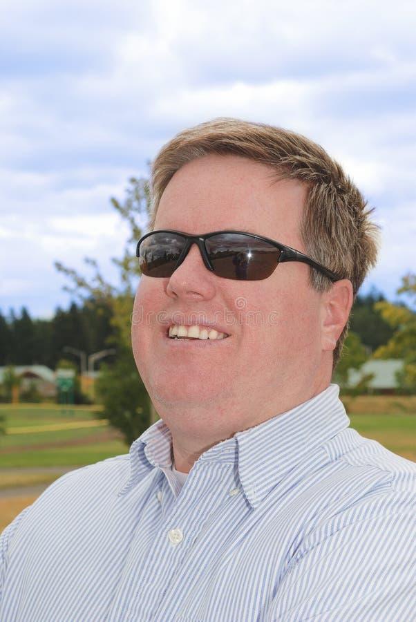 Homem novo feliz nos óculos de sol. foto de stock