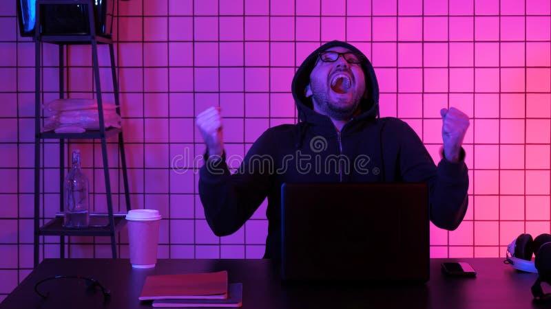 Homem novo feliz nos monóculos que olha o jogo de computador Reação emocional fotos de stock