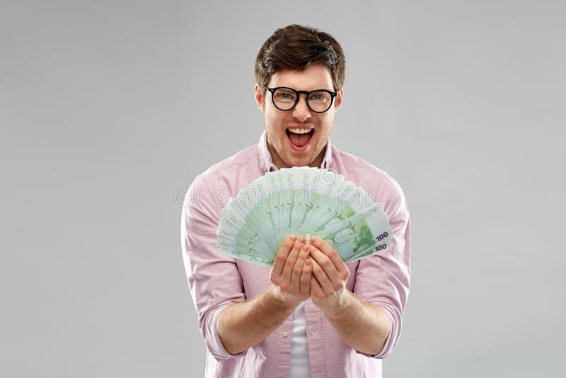Homem novo feliz nos vidros com o fã do euro- dinheiro imagem de stock