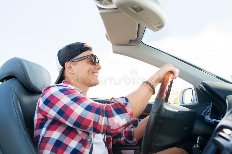 Homem novo feliz que conduz o carro convertível foto de stock