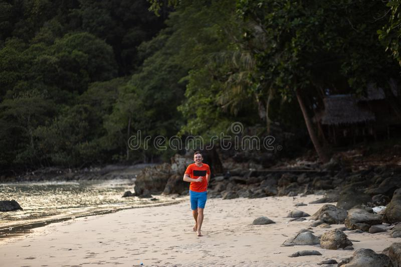 Homem novo feliz que corre em uma praia em Ko Chang, destino do curso de Tailândia em abril de 2018 - o melhor para a felicidade fotos de stock royalty free