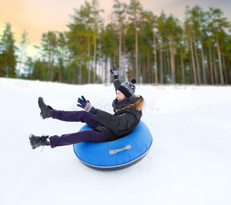 Homem novo feliz que desliza abaixo do monte no tubo da neve fotos de stock royalty free