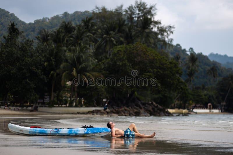 Homem novo feliz que encontra-se perto de um barco do caiaque em Ko Chang, destino do curso de Tailândia em abril de 2018 - o mel imagem de stock royalty free