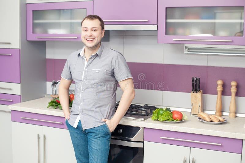 Homem novo feliz que está em sua cozinha moderna fotografia de stock
