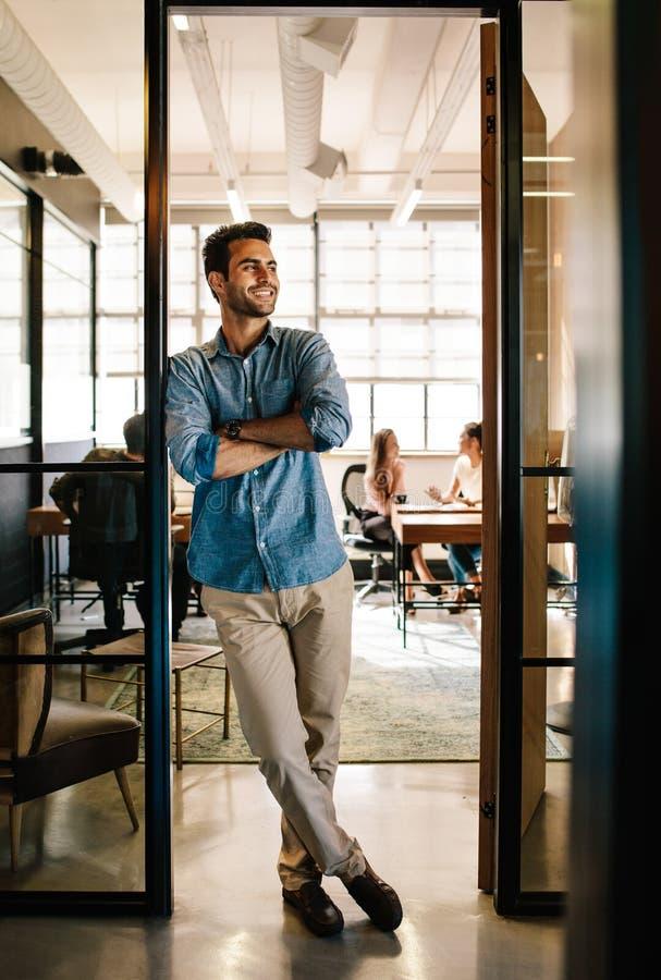 Homem novo feliz que está na entrada do escritório imagens de stock