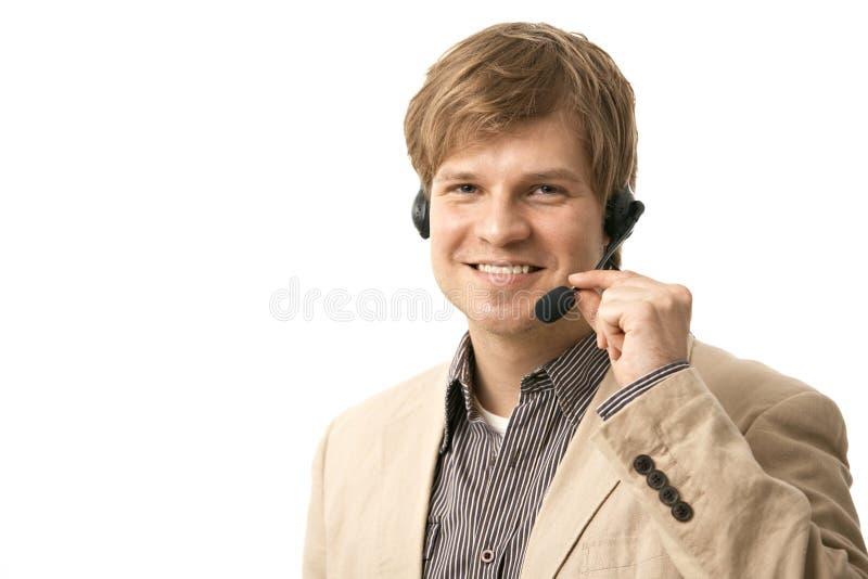 Homem novo feliz que fala em auriculares foto de stock royalty free