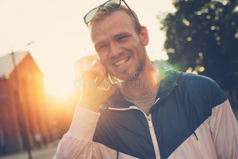 Homem novo feliz que fala no telefone celular na rua imagem de stock royalty free