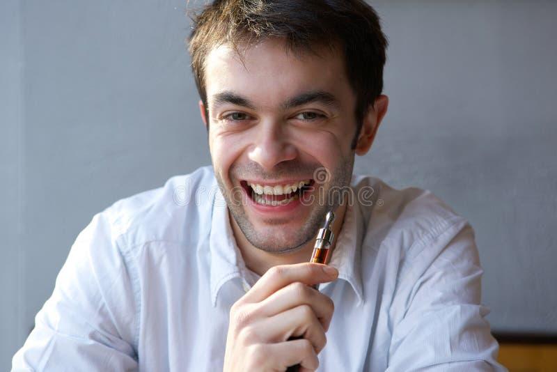 Homem novo feliz que guarda o cigarro bonde foto de stock