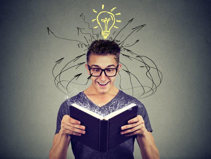 Homem novo feliz que lê um livro com a ampola acima da cabeça imagens de stock royalty free