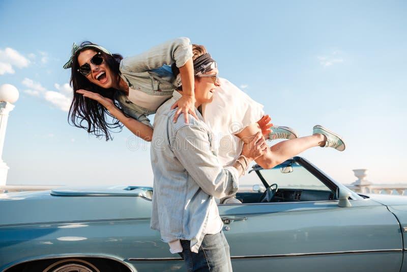 Homem novo feliz que leva sua mulher perto do carro do vintage fotos de stock