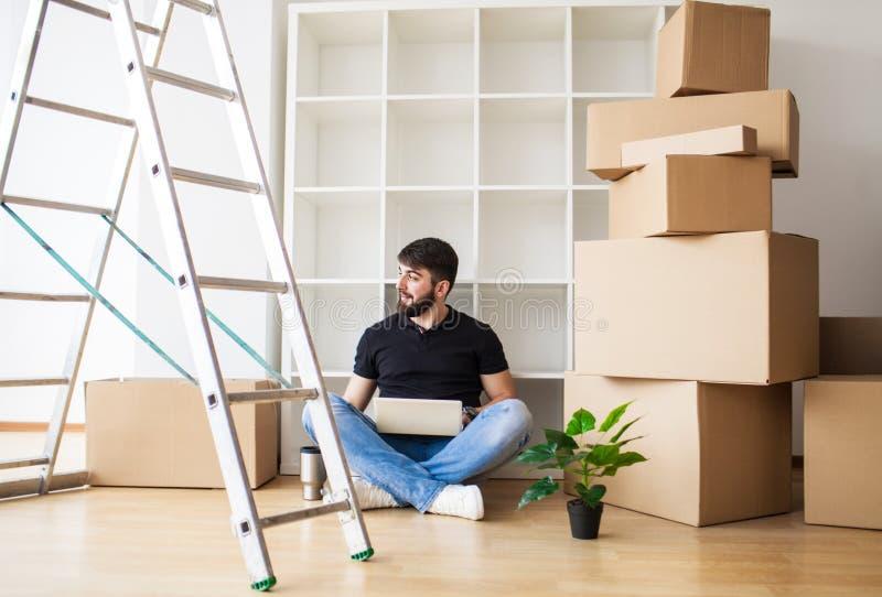 Homem novo feliz que move-se para a casa nova - tendo o divertimento imagens de stock