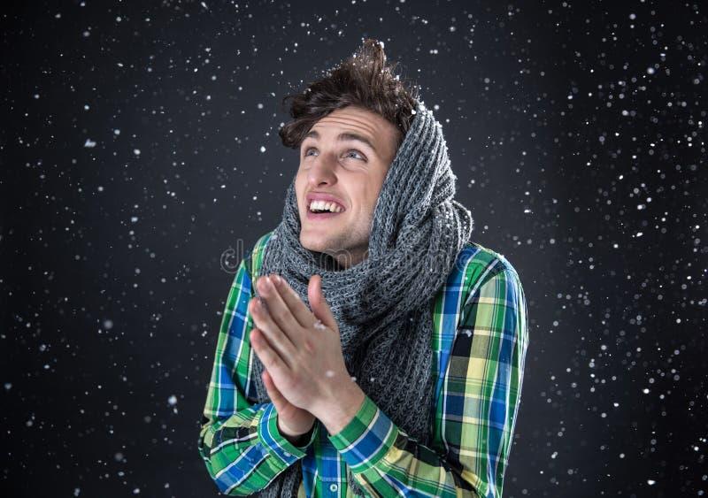Homem novo feliz que olha acima com neve fotos de stock royalty free