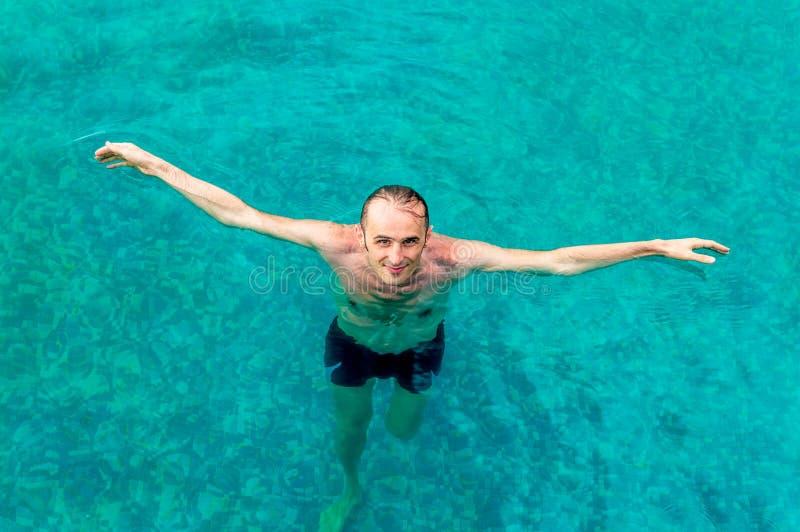 Homem novo feliz que olha acima e que sorri à câmera com braços abertos em uma piscina imagem de stock