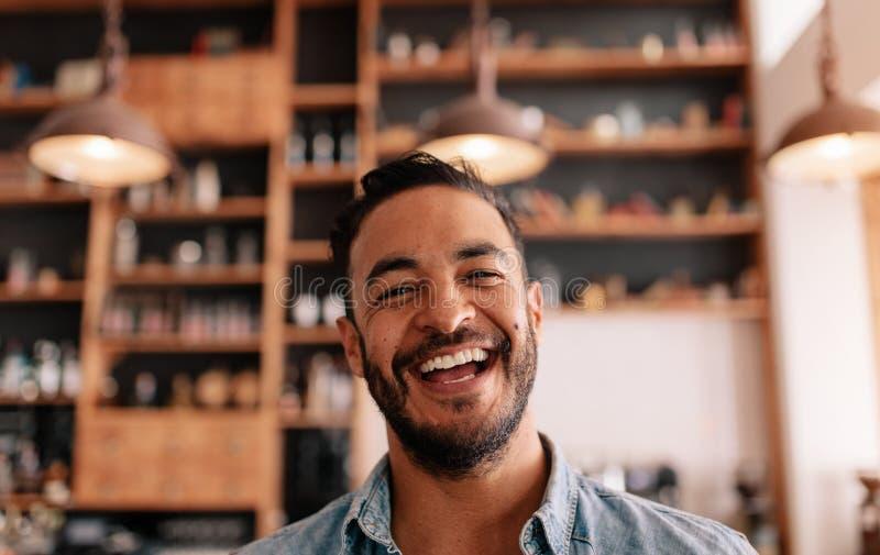 Homem novo feliz que ri em um café fotos de stock royalty free