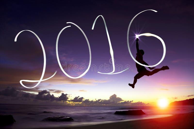Homem novo feliz que salta e que tira 2016 foto de stock royalty free