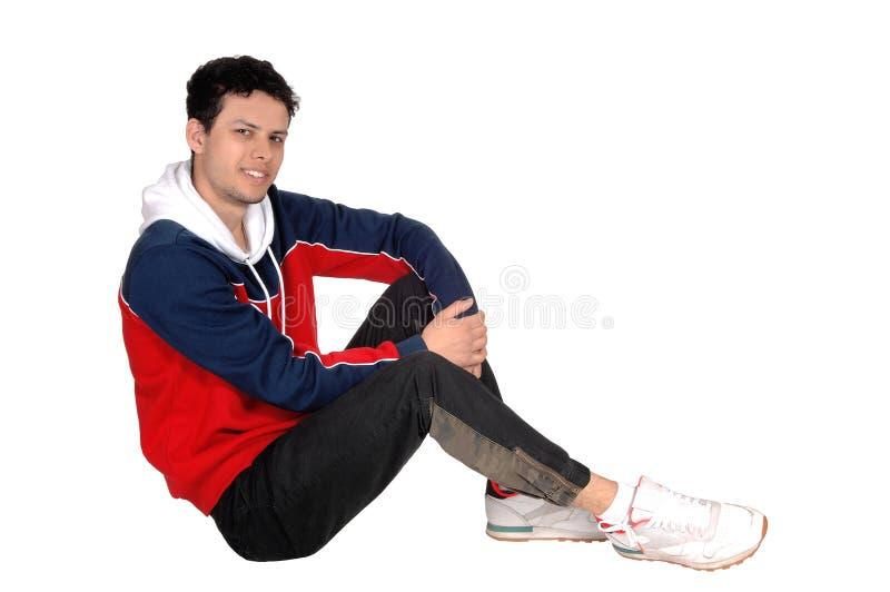 Homem novo feliz que senta-se no assoalho que descansa do exercício imagem de stock