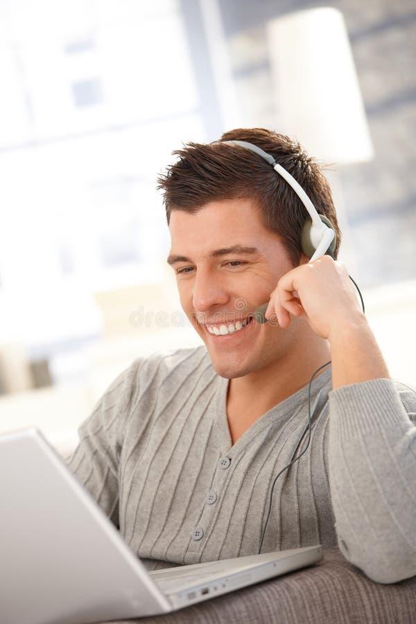 Homem novo feliz que usa o portátil e os auriculares imagem de stock royalty free