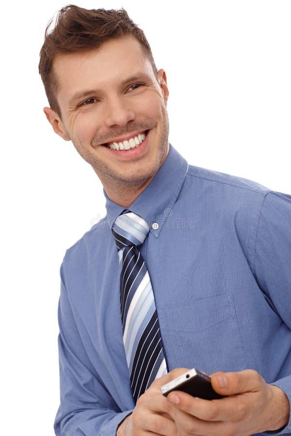 Homem novo feliz que usa o telefone celular foto de stock royalty free