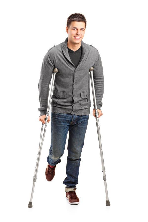 Homem novo ferido em muletas foto de stock royalty free