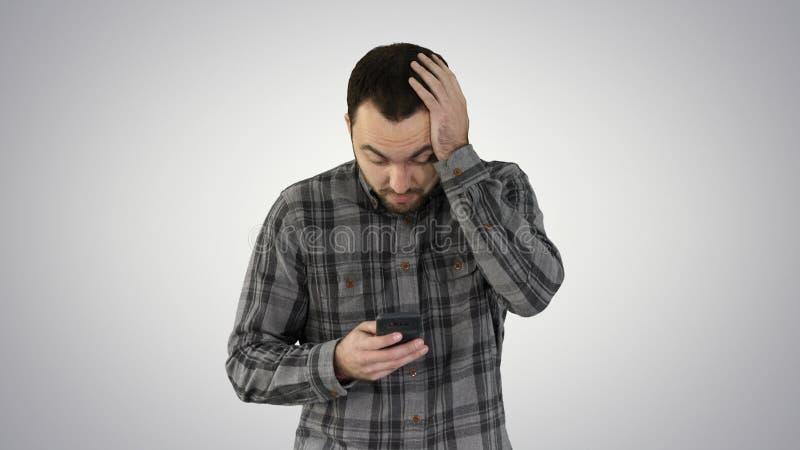 Homem novo forçado chocado surpreendido, horrorizado e perturbado, pelo que vê em seu telefone celular no fundo do inclinação foto de stock royalty free