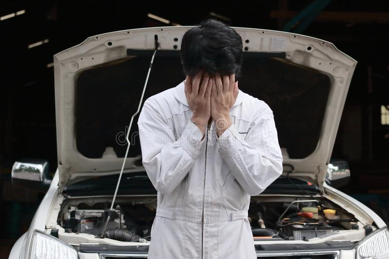 Homem novo forçado frustrante do mecânico no uniforme branco que cobre sua cara com as mãos contra o carro na capa aberta na gara fotografia de stock