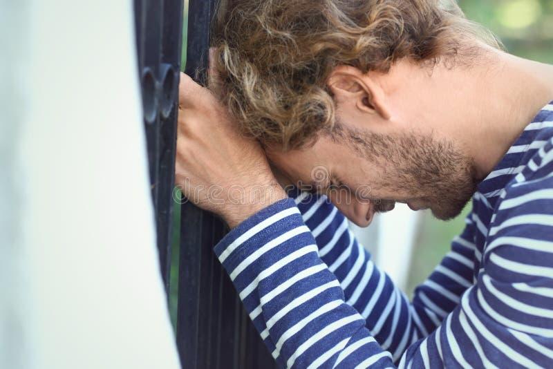 Homem novo forçado perto da cerca fora foto de stock