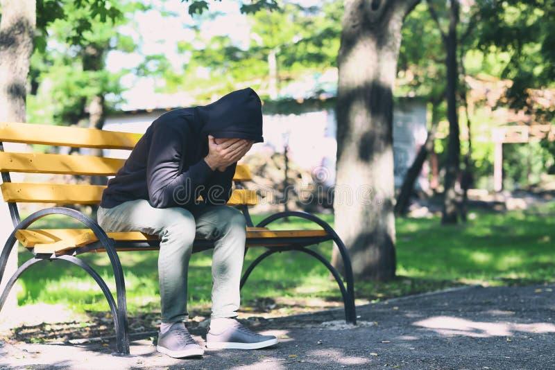 Homem novo forçado que senta-se no banco fora imagem de stock