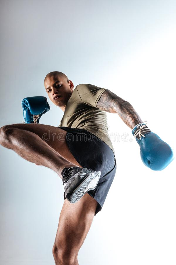 Homem novo forte que faz movimentos de combate rápidos fotografia de stock royalty free