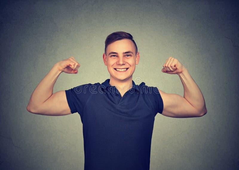 Homem novo forte que mostra o bíceps fotografia de stock