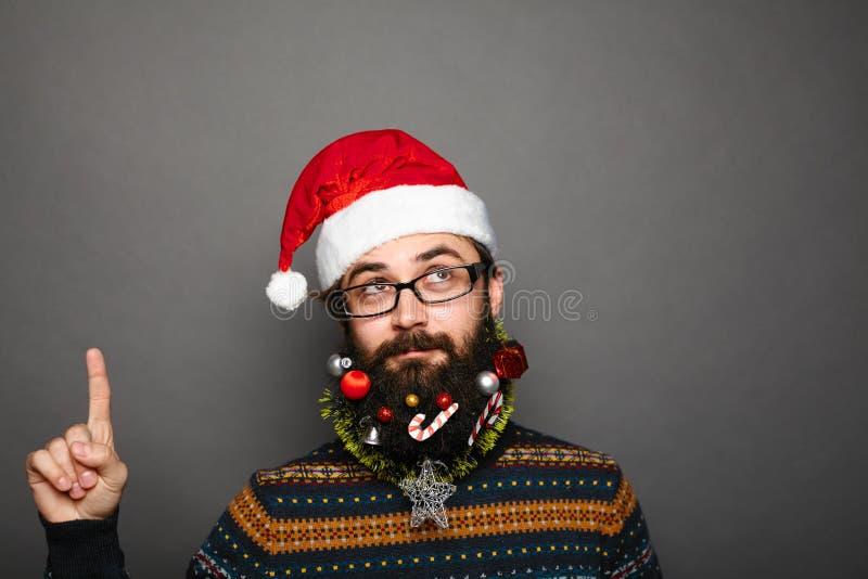 Homem novo Geeky no chapéu de Papai Noel que aponta acima imagem de stock royalty free