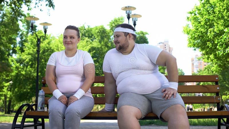 Homem novo gordo que coloca ao corrente com a senhora consideravelmente obeso que senta-se no parque, confiança imagens de stock royalty free