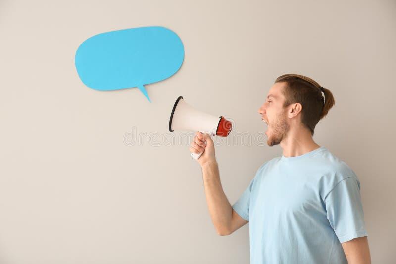 Homem novo gritando com megafone e bolha vazia do discurso no fundo claro fotos de stock royalty free