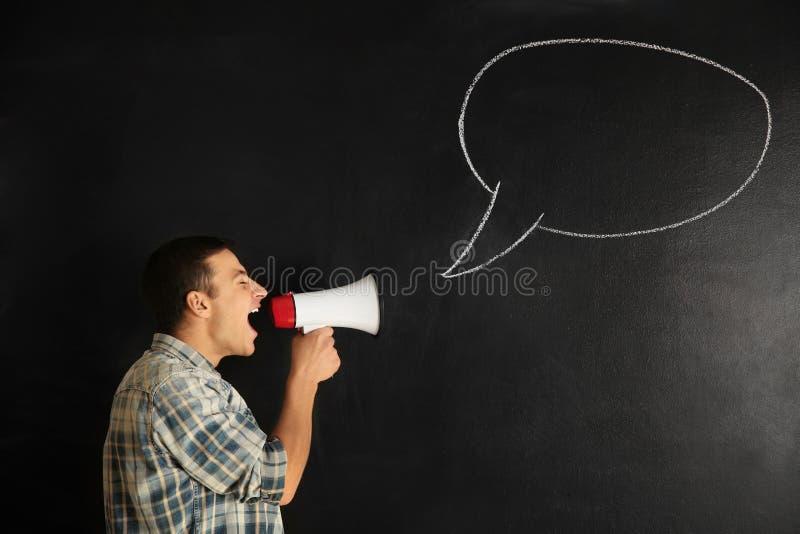 Homem novo gritando com o megafone perto da bolha tirada do discurso no fundo escuro fotos de stock royalty free