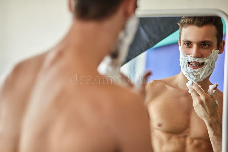 Homem novo impressionante feliz com espuma em sua cara que olha o espelho no banheiro fotos de stock
