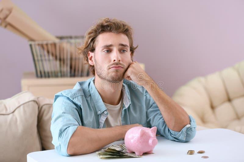 Homem novo incomodado com o mealheiro na tabela imagens de stock