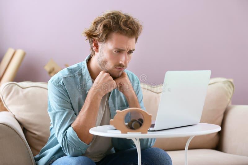 Homem novo incomodado que conta o salário em casa imagem de stock royalty free