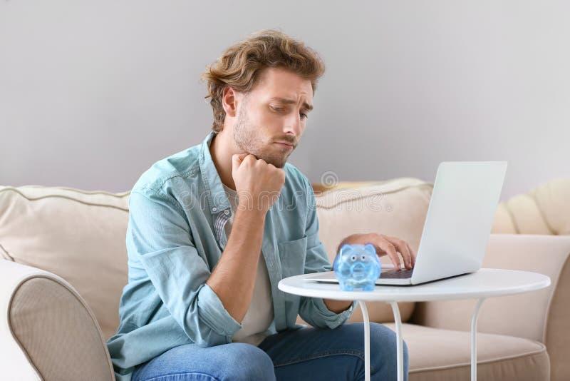 Homem novo incomodado que conta o salário em casa imagens de stock royalty free