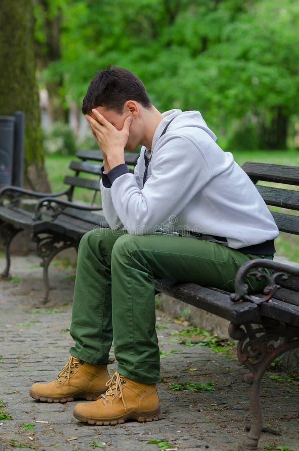 Homem novo incomodado que senta-se no parque imagem de stock