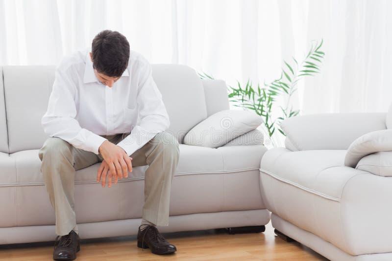 Homem novo incomodado que senta-se no sofá fotos de stock
