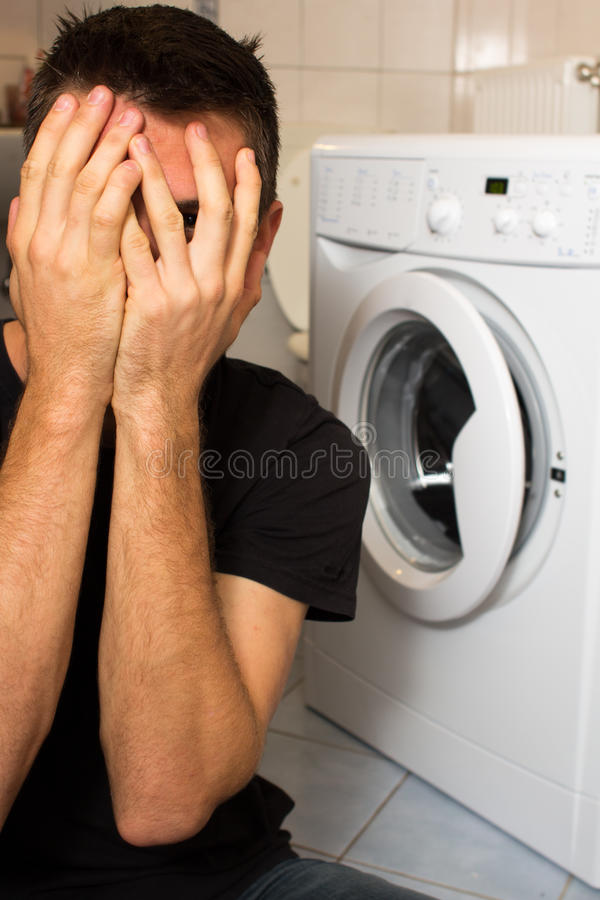Homem novo infeliz com mashine de lavagem imagem de stock