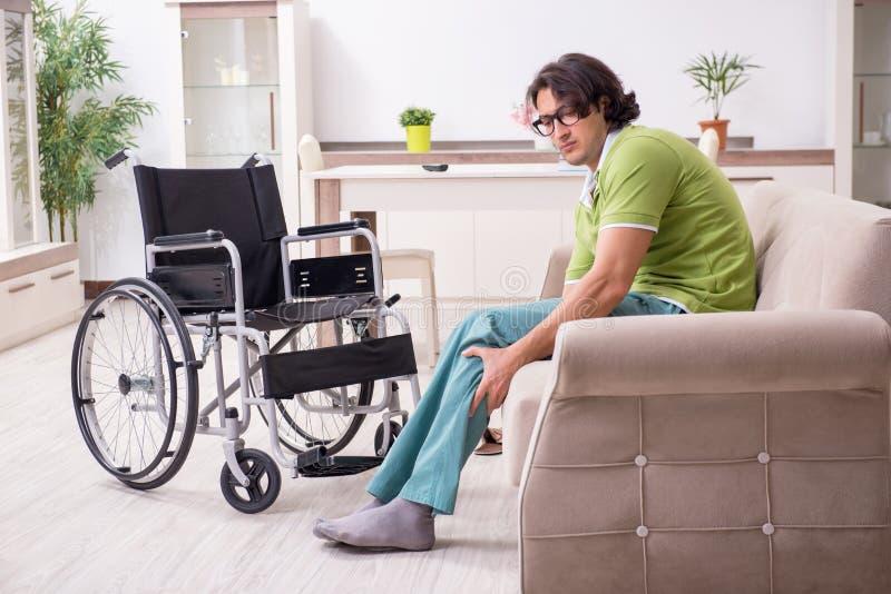 Homem novo inválido na cadeira de rodas que sofre em casa fotografia de stock royalty free