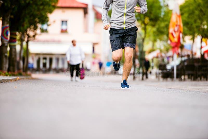 Homem novo irreconhecível que corre na cidade, rua principal imagem de stock