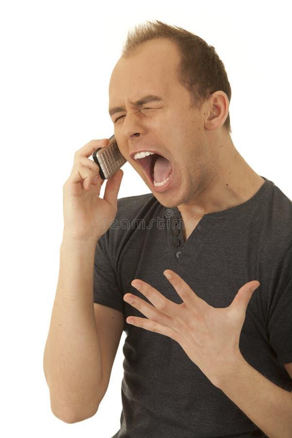 Homem novo irritado com um telefone foto de stock