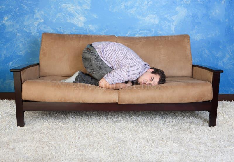Homem novo irritado no sofá fotos de stock