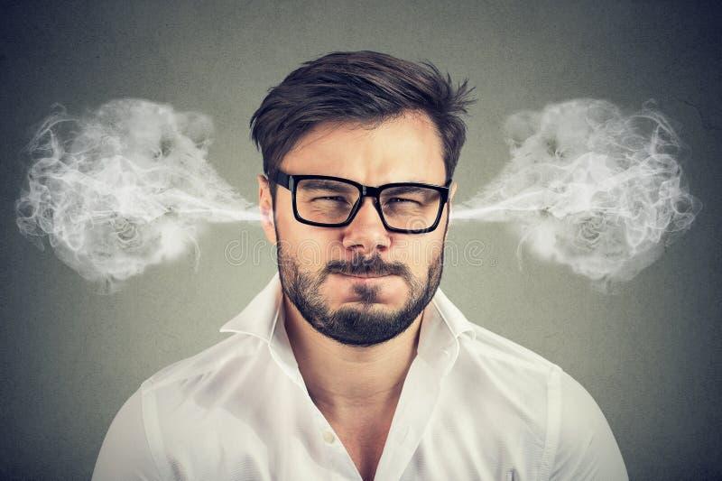 Homem novo irritado, vapor de sopro que sai das orelhas imagens de stock royalty free